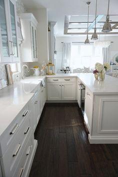 cuisine blanc laqué, avec parquet en marron foncé, trois luminaires suspendus au-dessus de l'îlot, meubles muraux blancs poignées couleur argent, vitrine en verre