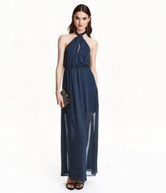 Lys korall. En lang halterneck-kjole i krinklet chiffon. Kjolen er omslagslagt foran og knappes med hempe i nakken. Bar rygg med elastikk øverst. Avskåret i