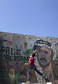 A Palestinian youth throws a stone as he stands against a mural painting of late Palestinian leader Yasser Arafat Israel's separation barrier at the Qalandia crossing in the occupied West Bank during protests on May 15, 2012, marking Nakba day, which commemorates the exodus of hundreds of thousands of their kin after the establishment of Israel state in 1948. AFP PHOTO/JACK GUEZ (Photo credit should read JACK GUEZ/AFP/GettyImages) 2012 AFP