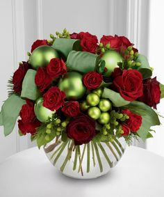 #TheFlowers Holiday Bowl Arrangement. Red roses and spray roses whimsically accented with green hypericum berries, green glass holiday balls, and green ribbon artfully arranged in a clear glass bubble bowl vase. http://www.carithers.com/product.cfm/iteID/2908