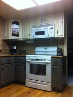 knotty alder kitchen cabinets with antique glaze. uppers are cream, lowers are green/gray