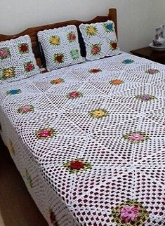 Here is a sober design crocheted with the white colored yarn and the flowers are multi-colored with the green leaves around them.Enhance the Beauty of Your Beds with Crochet Bedspreads Crochet Bedspread Pattern, Crochet Quilt, Granny Square Crochet Pattern, Crochet Flower Patterns, Crochet Stitches Patterns, Crochet Squares, Crochet Designs, Crochet Flowers, Crochet Potholders