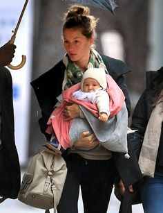 Vivians Animal Ears! Gisele carried her baby daughter Vivian (wearing an adorable hat) during a rainy morning in NYC April 12.