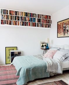 White Bedroom with Bookshelves Hung High on Wall and Woven Rug