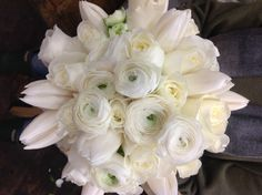 Ranunculus create a central focal point and then this bouquet is filled out with white roses (Tibet) and white tulips.