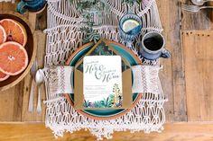 mesa posta com toalha de macramê, sousplat de barro e pratos de cerâmica.