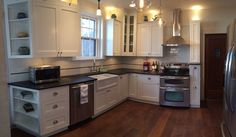 Custom white kitchen with inset cabinets, subway tile w/ glass bar liner,  soapstone countertops and new wood flooring. Caldera Design LLC