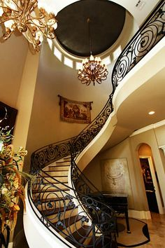 Impressive hanging staircase with custom designed iron railings. Enormous chandelier in a huge rotunda. Staircase has mahogany hardwood landings & travertine risers.