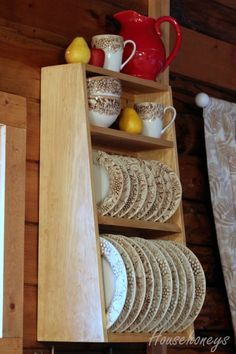 Wall hung plate rack ... only the bottom part needs to be wide enough for dinner plates. The tapered sides makes it less of an obtrusive box. Also shows off more of the small plates.