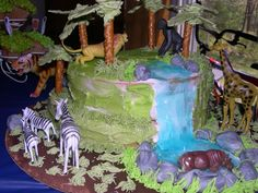 this is a jungle themed cake I did for my son's 2nd birthday. the waterfall is piping gel and the animals are plastic other than that e...