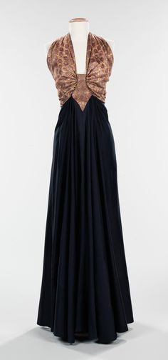 """""""From the Arabic"""" Evening Dress, Elizabeth Hawes (American, 1903–1971), fall/winter 1939, silk, metal, wool, lamé. """"...The detail at the center front of the bodice of the dress is a similar form to that of metal decorative ornaments from the same culture and it appears as if it catches the fabric of the halter-style bodice, creating a gathered effect. At the bottom of the appliqué, the skirt is tucked at either side of the point and gathered, creating a three-dimensional effect..."""""""