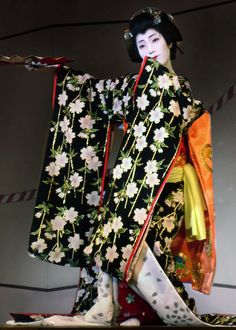 Tsunesono, a geiko of Gion, strikes a feminine pose...