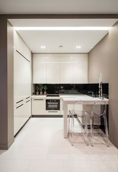 Une petite cuisine moderne blanche dans un renfoncement, avec des chaises hautes transparentes. Seules les 3 plantes dans le coin apportent une touche de couleur. [vu sur diegoenriquefinol.com]