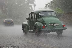 Driving you mad: A Morris Minor battles through the downpours on a wet start to the Bank Holiday weekend