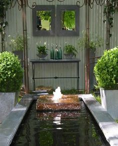 A pond constructed with the substance behind a steel pavilion and flanked by two large Buxus bulbs.