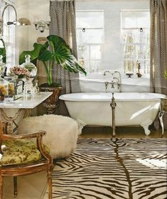 beautiful bathroom with cast iron tub, drapes, over-sized house plant, zebra rug, vanity, and arm chair