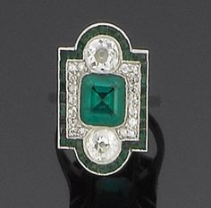 An art deco emerald and diamond ring, circa 1925  The geometric plaque set to the centre with a step-cut emerald between two old brilliant-cut diamonds, within a single-cut diamond border and a further calibré-cut emerald surround, principal diamonds approx. 1.00ct. total