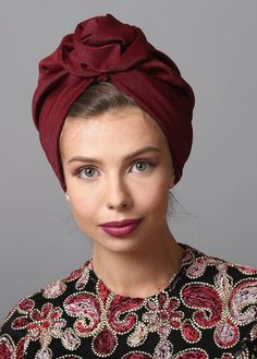 Flower style turban in burgundy. Perfect for holidays and special occasions. The Turban is stretchy, light, and comfortable. The back of the turban has an elastic strip sewn in for comfort and stability. This versatile turban can be worn as a full or