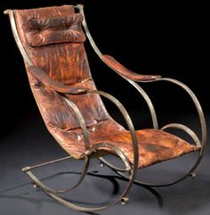 antiques price guide, antiques priceguide, furniture, England, A Victorian steel and leather rocking chair, mid 19th century, attributed to R. W. Winfield and Company, Birmingham, England, the antique leather cover of sling form with an attached headrest, joined to a curvilinear metal frame.