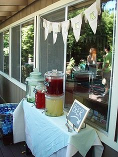 "dessert table under window, fabric or plastic tablecloth as window curtain and red garland sign with ""graduation is sweet"""