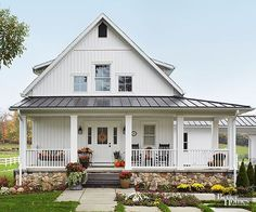 White trim, white siding, and white railings give this farmhouse spick-and-span appeal. A black-painted gable vent and charcoal gray steps take their color cue from the home's metal roof. The dark paint finishes and white surfaces enhance the home's historic country profile and complement its river rock foundation.
