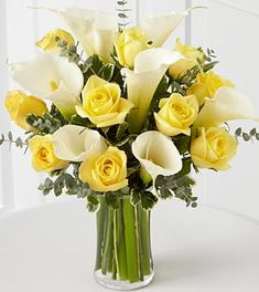 centerpieces yellow roses and calla lilies.... we can make it with red and yellow roses and a different green
