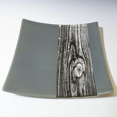 This platter has a section of clear glass bordered by opaque light gray glass, and features a woodgrain pattern printed in black enamel, then fused in a kiln to about 1400 degrees. The fused piece is