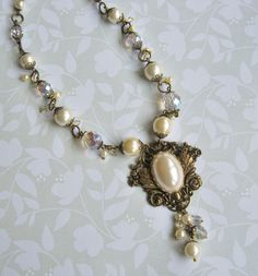 June Bridal Jewelry Challenge #3 from Novegatti Designs. A simple classic necklace with B'Sue brass and 'pearl' cabochon, and vintage and new pearl beads and Czech faceted clear AB beads in the chain and dangle. I made a similar one last year, and like the classic look of it. www.facebook.com/NovegattiDesigns