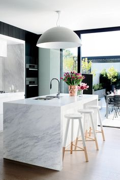 over sized pendant light over the kitchen island marble bench is in perfect proportion