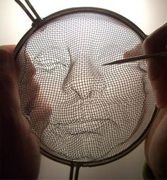 Isaac Cordal created three-dimensional grid faces and used street lights to cast their shadows onto the pavement in London, England.  3D faces were sculpted into the metal grids of several kitchen strainers.