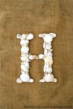 Sea Shell Monogram - Pine cones and acorns would be more my style :) Attach a burlap ribbon to hang it on the door.