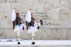 Greece, Athens, Soldiers wearing traditional clothing walking on Syntagma square