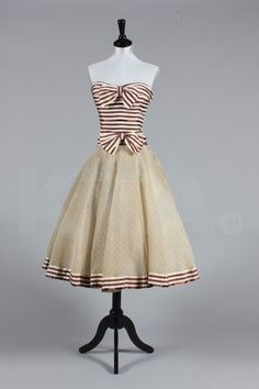Chanel couture striped satin cocktail dress, Spring-Summer, 1956, labelled and numbered 4078, the boned strapless bodice striped in burgundy/brown and ivory, with matching bows and band to hem, spotted beige/ivory organdy skirt and lined in another layer of organdy, bust 86cm, 34in, waist 61cm, 24in A similar gown was photographed by Seeberger in 'Femme Chic' no 466 Spring-Summer, 1956, p.166.