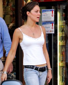 JUNE 2005 Cute and casual! The then-Kate Middleton rocks a simple white spaghetti strap top and a black braided belt with jeans.