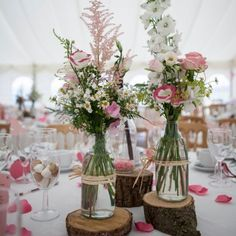 Real Weddings - In Bliss Weddings: The centerpieces by florist, Sally Richardson, were made of milk bottles filled with assorted white and pink flowers. The milk bottles sat on cut tree branches, which was a perfect way to bring their country theme inside to their reception room.