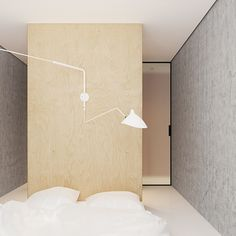 Bedroom with bed on floor and large white wall sconce. Gorgeous small minimalistic apartment / Emil Dervish