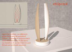 """Una vita insieme...un abbraccio eterno sulla base di unicità di Intenti...esaltazione """"reciproca"""" delle virtù attraverso la """"luce"""" dell'altro. Un tentativo di sintetizzare in una forma, una profonda sostanza. Lampada da tavolo, con sistema di illuminazione a led, in legno con finitura trasparente,  base e parte interna riflettente laccata bianca; la lampada è dotata inoltre di un piccolo accessorio porta candela."""