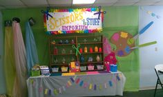 Scissors and Stuff Emporium - giant paint palette; shelves, bunting on table.