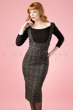Show your curves in this 50s Natalia Braces High Waist Pencil Skirt!  Spice up your work wardrobe with Natalia because she's sassy, classy AND chic! The flattering high waist, adjustable braces and tight fit show off your figure without revealing any skin ;-) Made from a stunning and firm cotton blend with a light stretch and a dark grey and red check and is finished off with 3 large faux buttons at the front. Wear with an elegant top for a classy curvalicious fifties look that's sui...
