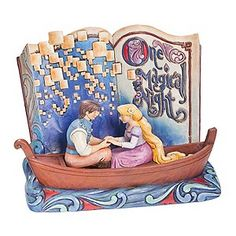 An inspired Disney Traditions hand painted figurine depicting Disney fairytale characters from Disney's Tangled. A colourful open book depicting the words One Magical Night forms a stunning backdrop to characters Rapunzel and Flynn on a romantic evening boat ride.