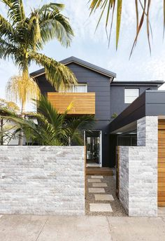 The facade of this tropical resort-style home is painted in bold 'Black Caviar' by Dulux, contrasting with the timber accents and 'Dogal' marble cladding on the front fence. Coastal Living Rooms, Coastal Homes, Coastal Decor, Modern Coastal, Coastal Entryway, Coastal Rugs, Coastal Lighting, Coastal Cottage, Coastal Style