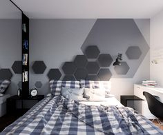 Lighter tones decorate the bedroom, which fades into shades of grey. A gingham duvet mirrors the beanbag in the lounge, while hexagonal wall motifs make their way across the room. A chalkboard question mark breaks the white wall, referring to the chalkboard wall in the kitchen.