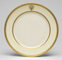 State dinner and dessert service of Woodrow Wilson (President 1913-1921)--Service Plate/Made in Trenton, New Jersey, United States, North and Central America 1918--Designed by Frank G. Holmes, American, 1878 - 1954. Made by Lenox Incorporated, Trenton, New Jersey, 1889 - present. Ordered from Dulin and Martin Company, Washington, D.C., 1899 - c. 1920. Porcelain with enamel and gilt decoration. Diameter: 9 3/4 inches (24.8 cm)