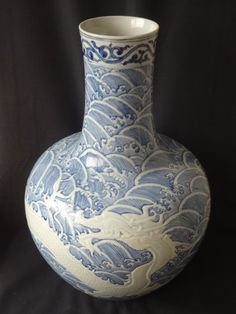 Rare Ming Dynasty Yongle Period Ball Shape Dragon Vase H 21 1/2 in. This vase is decorated with a low-relief carving of a dragon admist water waves. The cobalt blue glaze was locally produced as evidenced by its light color. This indicates that this vase was made during the early Yongle Period before the Yongle Emperor sent Changhe to the South of China to get the Smalt cobalt mineral.