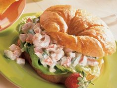 1 cup diced imitation crabmeat (surimi) 1 (4-oz.) pkg. frozen small shrimp, thawed 1 cup chopped seeded cucumber 1/2 cup purchased creamy cucumber salad dressing 4 croissants, split 4 leaves Bibb lettuce