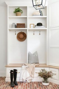 Fixed against a stunning red brick floor, a white built-in storage bench with a stained wood seat is fixed under white open lockers boasting a shiplap trim and brass hooks mounted beneath stacked shelves. Shiplap Trim, Oak Trim, Sofa Colors, Custom Cushions, Brick Flooring, Built In Storage, Pantry Storage, Ship Lap Walls, Red Bricks