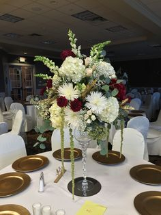 White hydrangea, white spider mum, burgundy carnations, snap dragons, cream spray roses, with some babies breath.