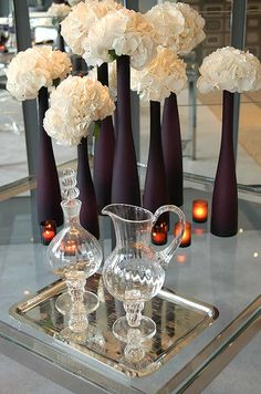Frosted purple vases of varying heights are accented with blooms of white hydrangeas.
