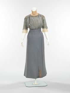 Suit, Walking  (a–c) House of Paquin  (French, 1891–1956)  Designer: (a–c) Mme. Jeanne Paquin (French, 1869–1936) Designer: (d) Thurn (American) Date: spring/summer 1910 Culture: French Medium: wool, metal, silk Dimensions: Length at CB (a): 22 in. (55.9 cm) Length at CB (b): 37 in. (94 cm) Length at CF (c): 17 1/2 in. (44.5 cm)