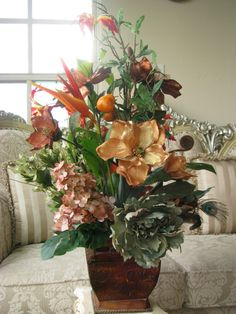 silk flowers of magnolias, birds of paradise, ginger, hydrengea, peony, ferns, feathers, lilies & tropical fruits